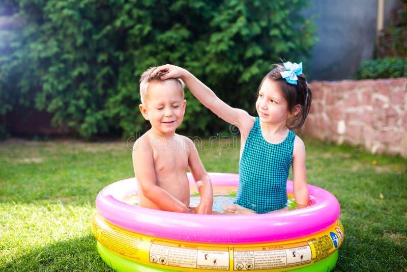 Temat jest dziecka wakacje Dwa Kaukaskiego dziecka brat i siostra, siedzą w umieszczam wokoło basenu z wodą w zdjęcia royalty free