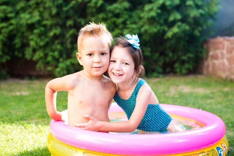 Temat jest dziecka wakacje Dwa Kaukaskiego dziecka brat i siostra, siedzą w umieszczam wokoło basenu z wodą w obraz stock