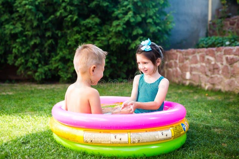 Temat jest dziecka wakacje Dwa Kaukaskiego dziecka brat i siostra, siedzą w umieszczam wokoło basenu z wodą w zdjęcie royalty free