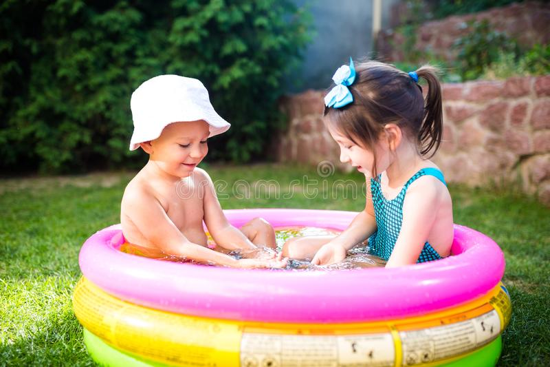 Temat jest dziecka wakacje Dwa Kaukaskiego dziecka brat i siostra, siedzą w umieszczam wokoło basenu z wodą w obraz royalty free