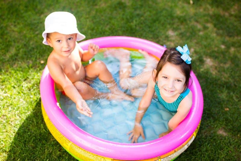 Temat jest dziecka wakacje Dwa Kaukaskiego dziecka brat i siostra, siedzą w umieszczam wokoło basenu z wodą w fotografia royalty free