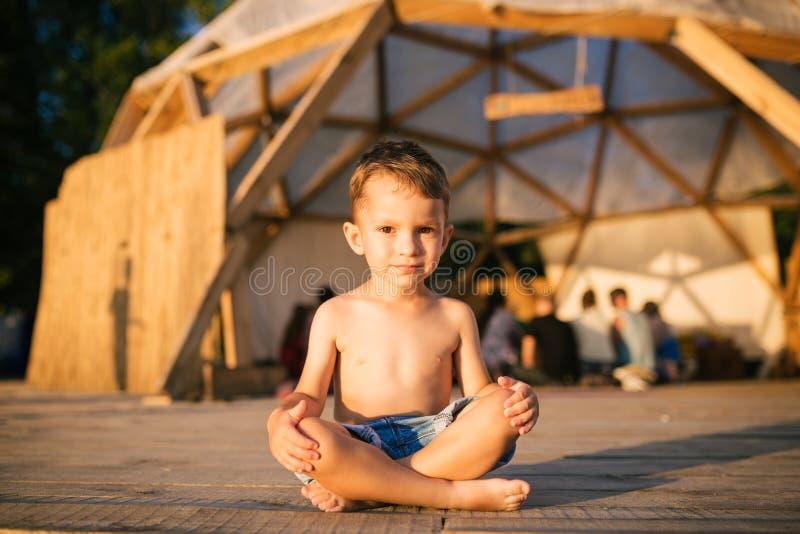 Temat jest joga i dziećmi Kaukaski chłopiec dziecko siedzi bosy skrzyżnego w lotosowej pozyci na drewnianej podłoga obrazy royalty free