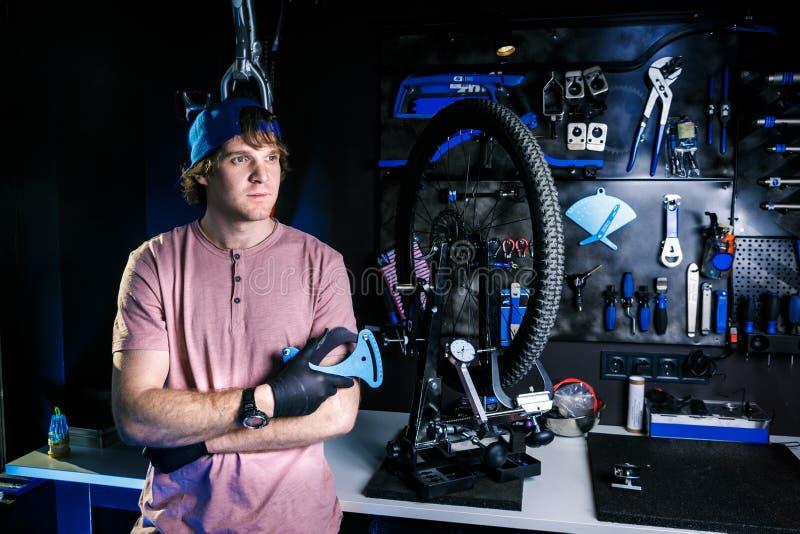 Temat mały biznes bicykl naprawa elegancki mężczyzna właściciel warsztatowi stojaki blisko maszyny dla naprawiać koło na tle fotografia royalty free