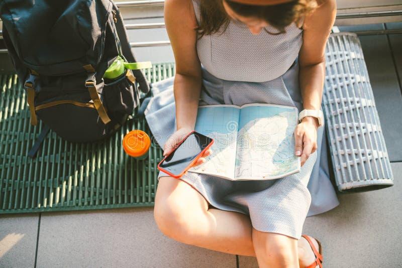 Temat podróży planowanie Odgórnego widoku ręk Kaukaska kobieta używa mądrze telefon i studiuje turystyczną mapę, przepustki trasa zdjęcia royalty free