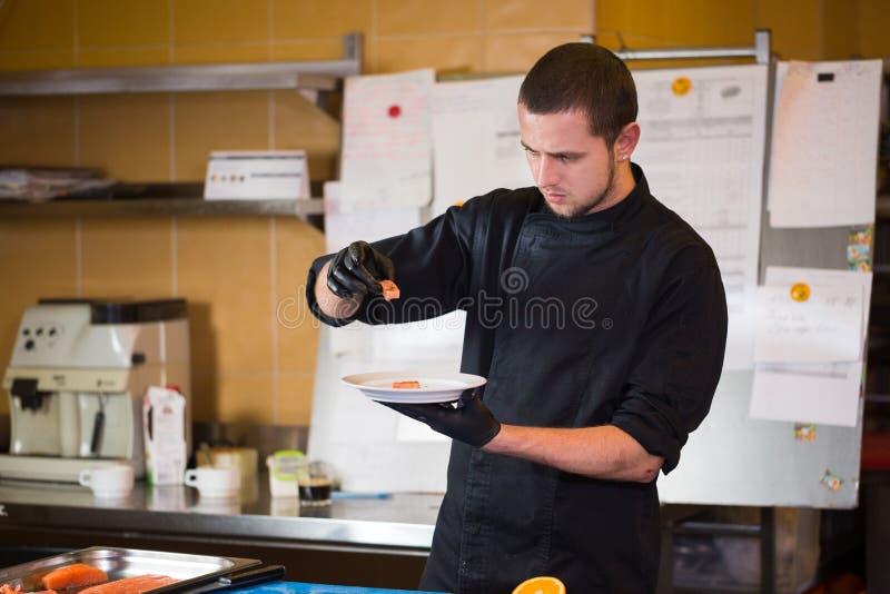 Tematu kucharstwo jest zawodem kucharstwo Portret Kaukaski mężczyzna w restauracyjnego kuchennego narządzania czerwony rybim prze fotografia stock