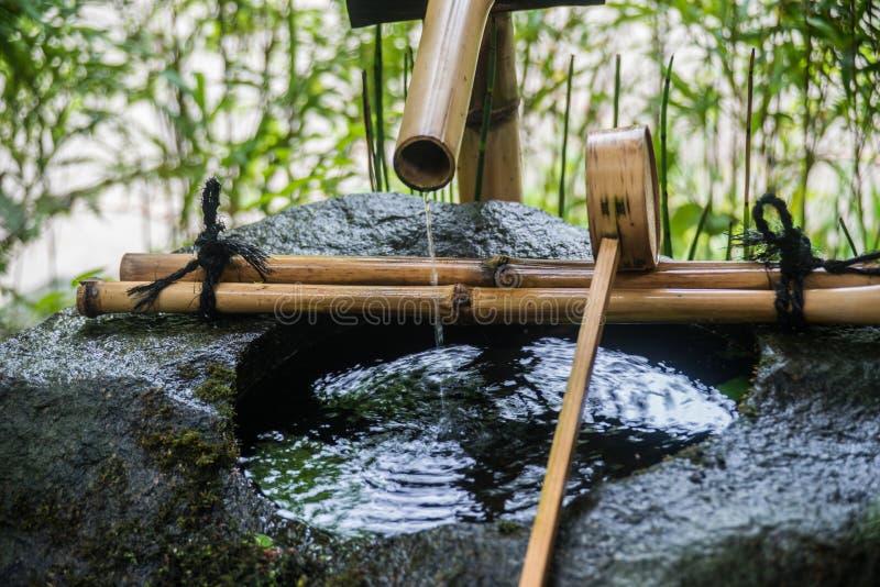 Temizuya purification rite Fountain dropping water. Temizuya purification rite Fountain stone and bamboo for hand and face washing stock photos