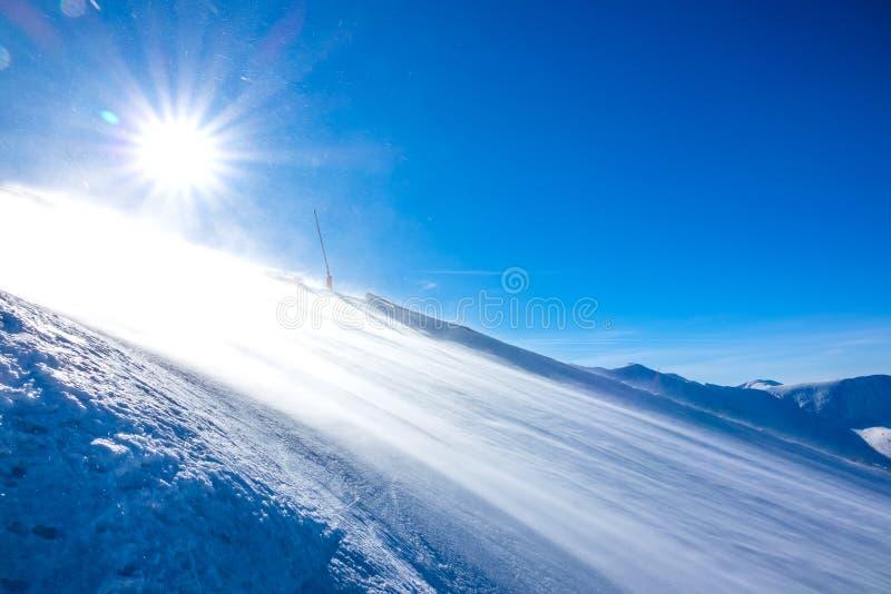Tempête de neige par temps ensoleillé sur une piste de ski vide photo stock