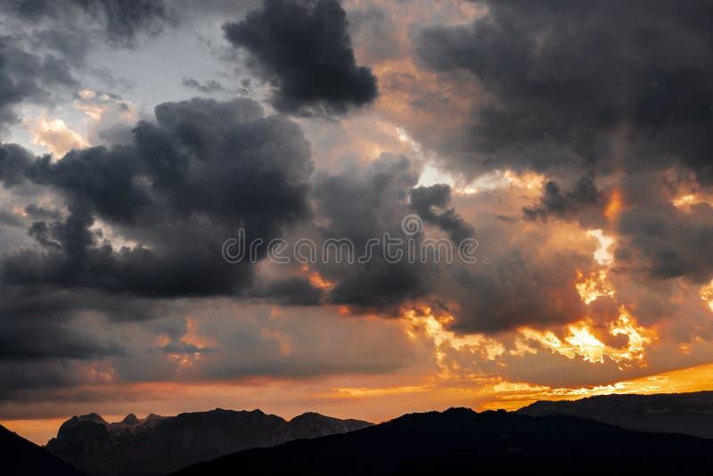 Tempête des nuages au coucher du soleil sur les montagnes photos stock