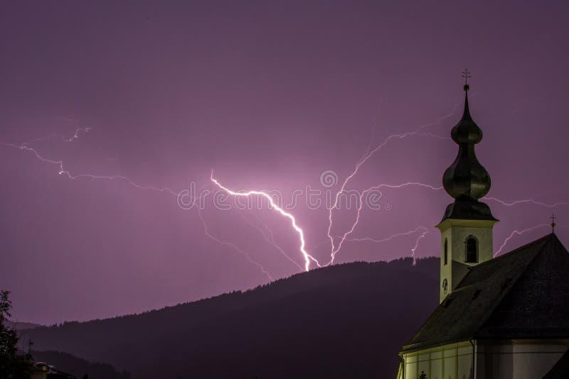 Tempête pourpre de foudre avec l'église dans le premier plan photographie stock