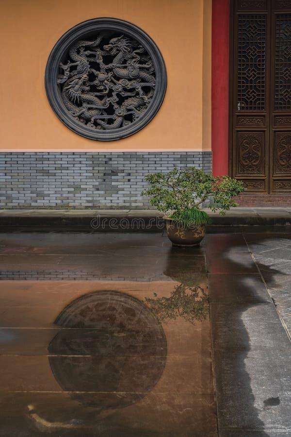 Tempelfönster från stenen och dess reflexion på ett vått golv royaltyfri bild