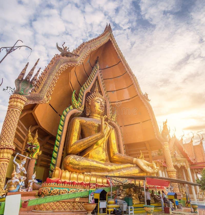 Tempelgränsmärke buddha med den guld- statyn för pagod på solnedgången royaltyfri fotografi