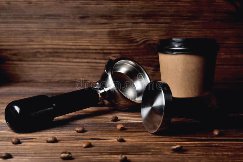 Temperament portafilter Kaffeebohne-Pappkaffeetasse auf einer braunen hölzernen Hintergrundnahaufnahme lizenzfreie stockbilder