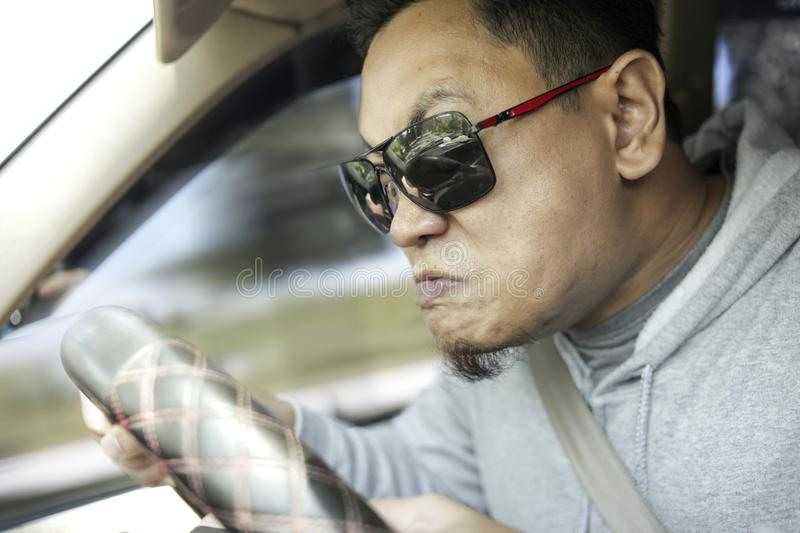 Temperamental Driver Concept, Angry Man Speeding Dangerously. Portrait of Asian male driver mad of other car criver, speeding his car with anger dangerously royalty free stock photos