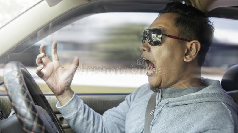 Temperamental Driver Concept, Angry Man Speeding Dangerously. Portrait of Asian male driver mad of other car criver stock photography