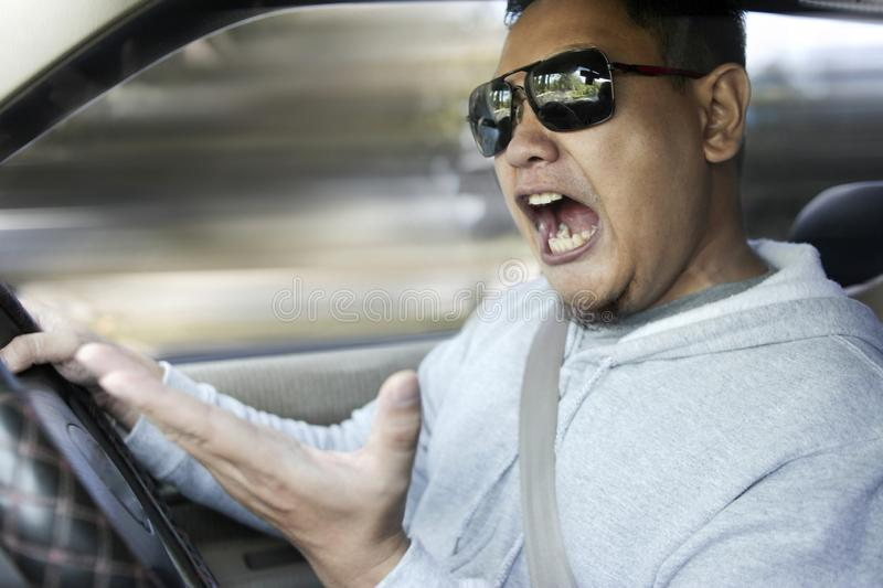 Temperamental Driver Concept, Angry Man Speeding Dangerously. Portrait of Asian male driver mad of other car criver royalty free stock image