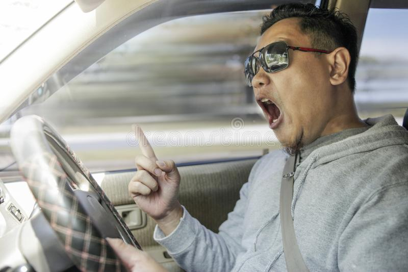 Temperamental Driver Concept, Angry Man Speeding Dangerously. Portrait of Asian male driver mad of other car criver royalty free stock photos