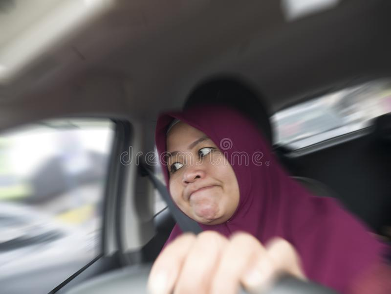 Temperamental Driver Concept, Angry Woman in Traffic Jam. Portrait of Asian muslim female driver mad of trapped in traffic jam,  mischievous reckless way of stock photos