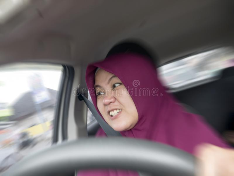 Temperamental Driver Concept, Angry Woman in Traffic Jam. Portrait of Asian muslim female driver mad of trapped in traffic jam,  mischievous reckless way of stock image