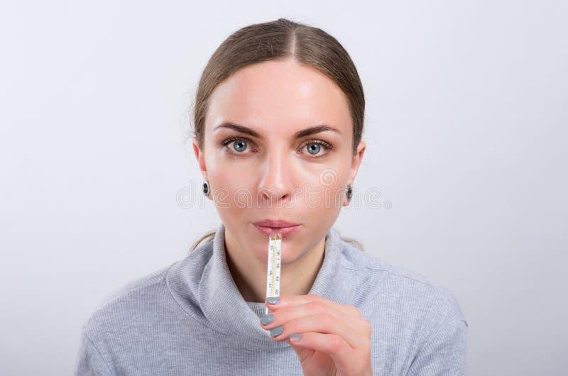 Temperatura corporea di misurazione della ragazza attraente su fondo leggero fotografia stock