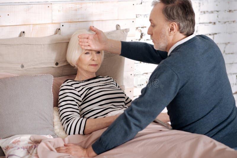 Temperatura de medición del hombre mayor de su esposa enferma imágenes de archivo libres de regalías