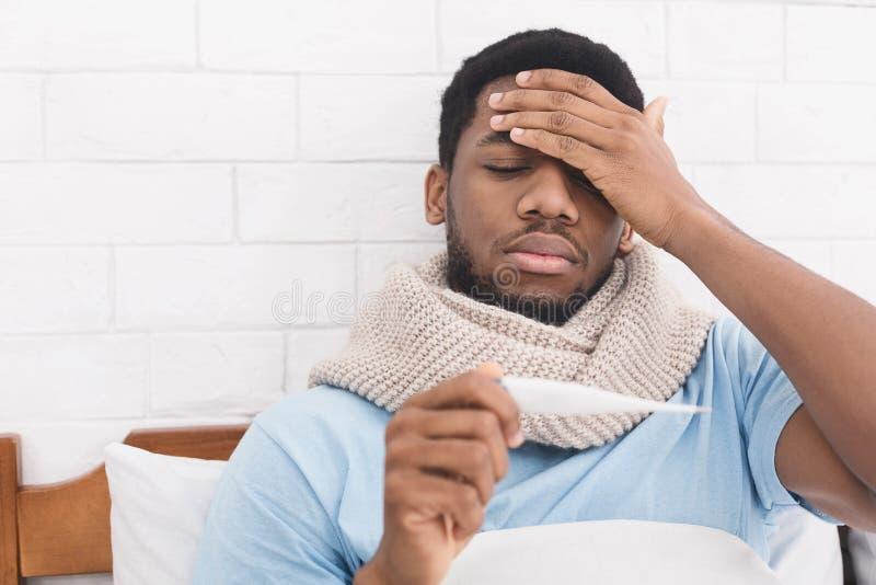 Temperatura del cuerpo de medición del hombre afroamericano enfermo en cama foto de archivo