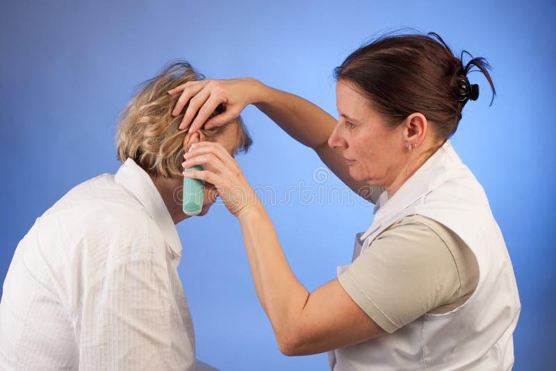 Temperatura di misurazione dell'infermiere alla donna senior fotografia stock