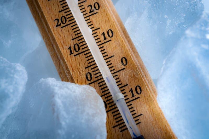 Temperaturas de congelação e conceito do tempo frio com fim acima em um termômetro do vintage cercado pelo sub azul da exibição d imagens de stock