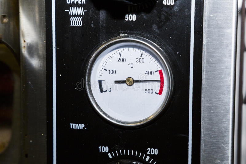 Temperature sensor on an industrial dirty black metal oven royalty free stock photography