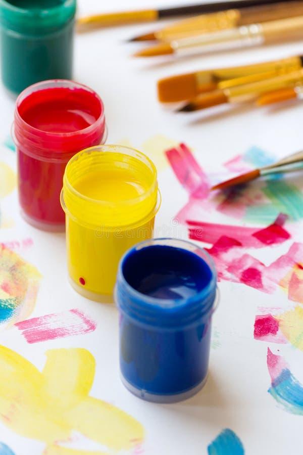 Temperaverf van verschillende kleuren groenachtig blauwe gele rode borstels op Witboekachtergrond met kleurrijke slagen Kunsten h stock afbeeldingen