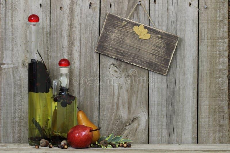 Tempere frascos do óleo com peras e anule o sinal de madeira fotografia de stock royalty free