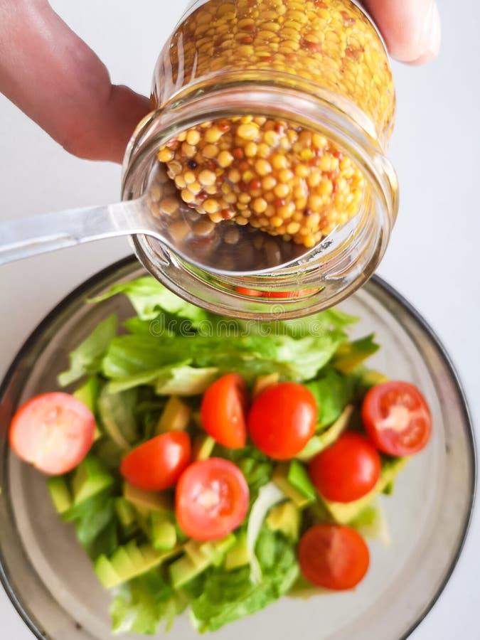 Tempero para a salada vegetal, adicionando a mostarda francesa à salada vegetal, alimento de Vigatarian, alimento saudável Derram imagens de stock
