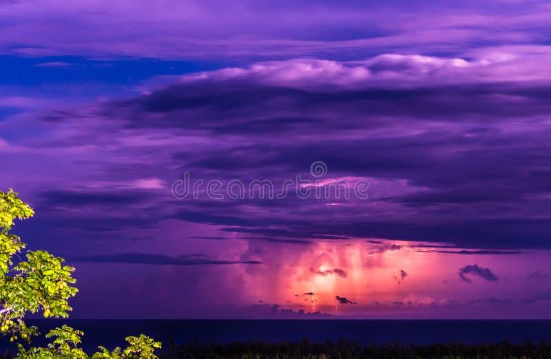 Tempesta d'alleggerimento sopra l'oceano alla notte Il fulmine serra colpire fotografia stock