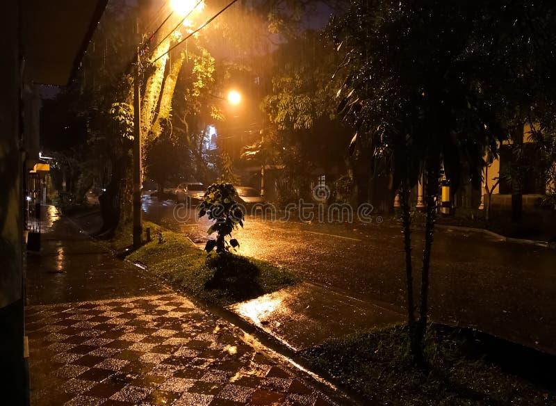 Tempesta della pioggia sopra una via scura immagini stock libere da diritti