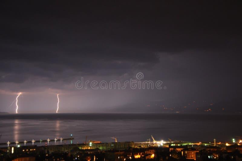 Tempesta di estate sopra il mare adriatico con il temporale due e la città di Rijeka di notte immagini stock