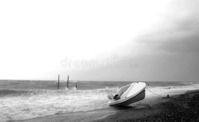 Tempesta sul mare con la barca invertita capovolta sulla spiaggia Foto in bianco e nero di Pechino, Cina fotografia stock