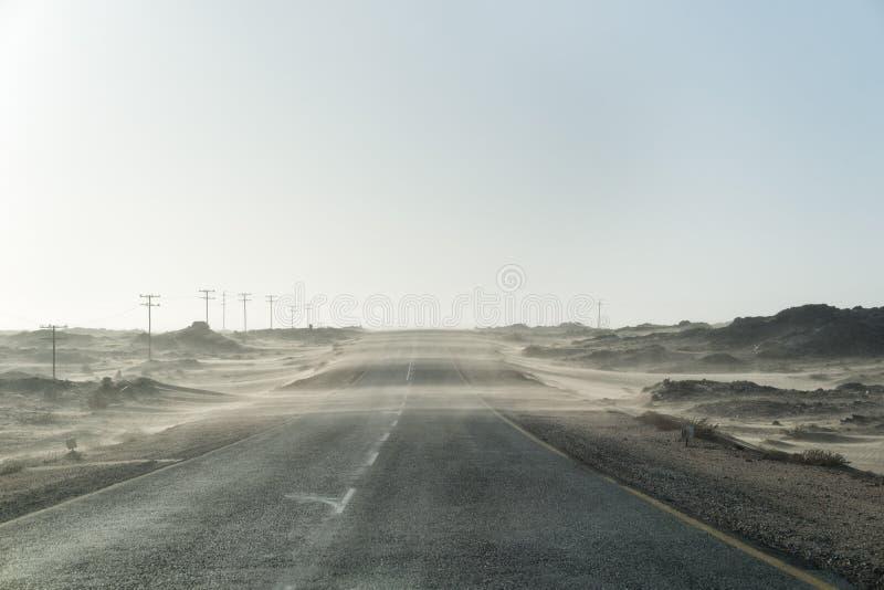Tempestad de arena a través del camino solo del desierto en i tomado Namibia meridional foto de archivo libre de regalías
