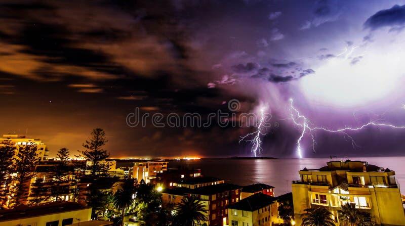 Tempestade da iluminação sobre uma cidade surfy da praia na noite fotografia de stock