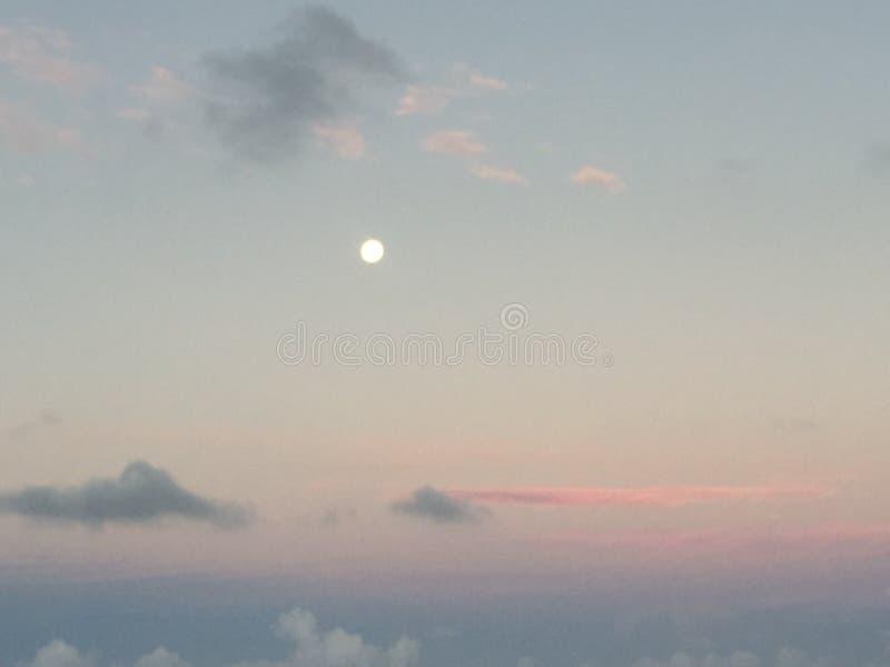 Tempestade distante com a lua já que aumenta no crepúsculo fotografia de stock
