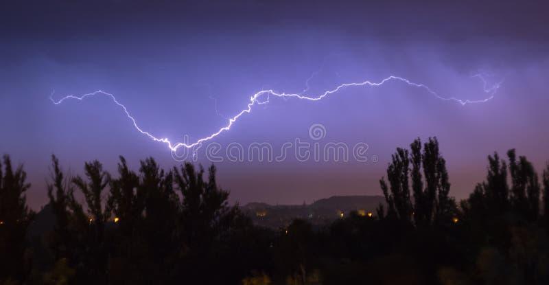 Tempestade do relâmpago da noite sobre a cidade na iluminação dramática azul imagens de stock