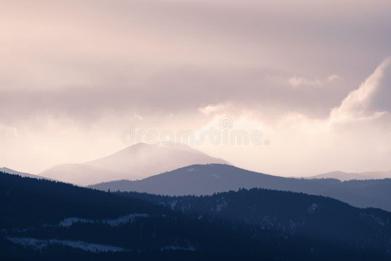 A tempestade dramática do inverno funde sobre uma paisagem estéril fria perto do por do sol fotografia de stock