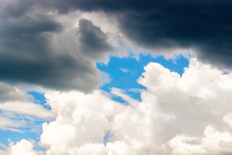 Tempestade escura e nuvens de cúmulo brancas no céu azul imagens de stock royalty free