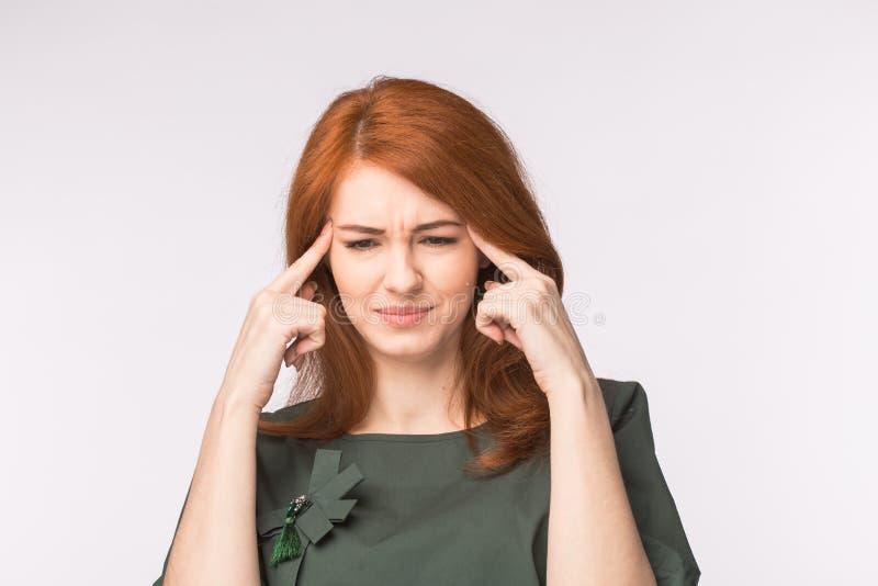 Tempie commoventi sollecitate della donna della testarossa e fondo di pensiero di bianco di persona dura Concetto di emicrania o  immagine stock