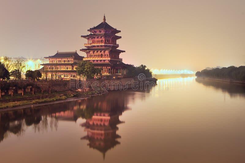 Tempio buddista con la pagoda accanto ad un fiume calmo durante la penombra, Nanchino, Cina fotografia stock libera da diritti