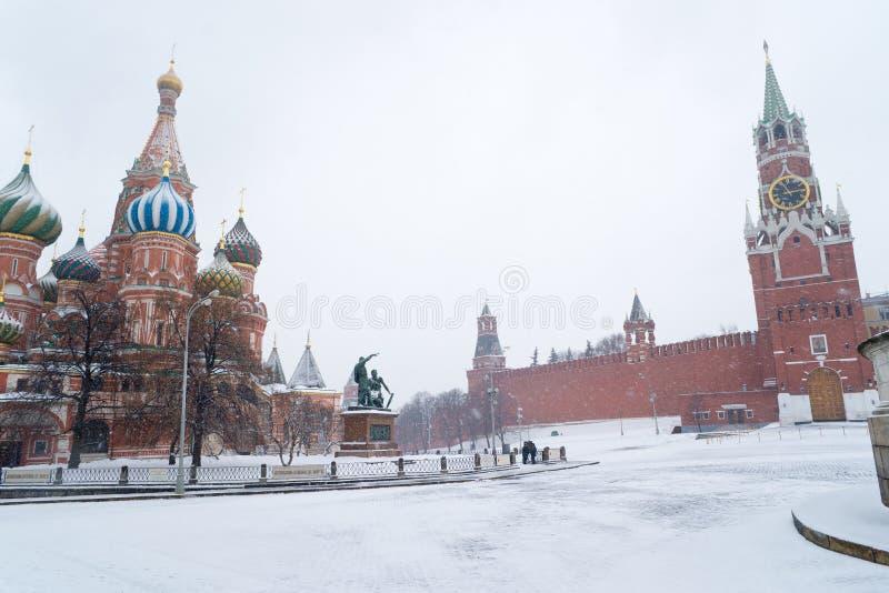 Tempio del basilico della st e torre di Spasskaya di Kremlin durante la bufera di neve fotografia stock libera da diritti