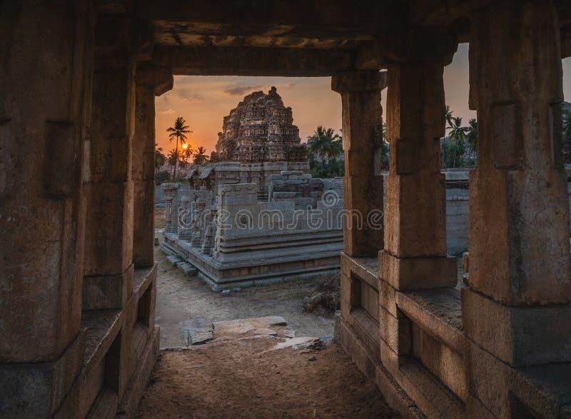 Tempio di Achyutaraya da un arco di pietra della porta in karnakata India di hampi ad alba con nuvoloso fotografia stock libera da diritti