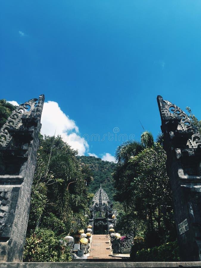 Tempio di Bali al giorno soleggiato con le montagne a fondo, Indonesia fotografia stock libera da diritti