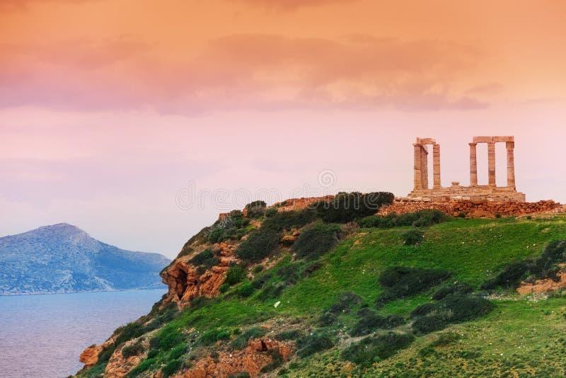 Tempio di Poseidon sulla collina verde vicino al mare, Grecia fotografia stock libera da diritti