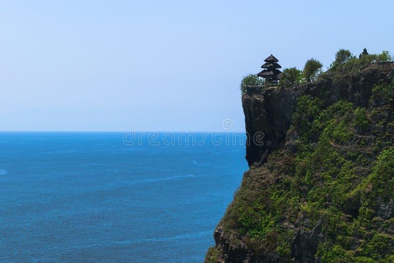 Tempio di uluwatu del luhur di Pura sulla scogliera con la bella vista di Oceano Indiano blu in Bali, Indonesia fotografia stock libera da diritti