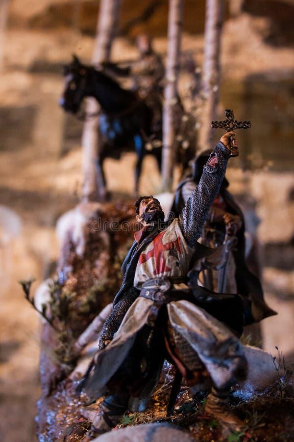 Templar骑士拿着十字架的和更多骑士的雕塑后边 免版税库存图片