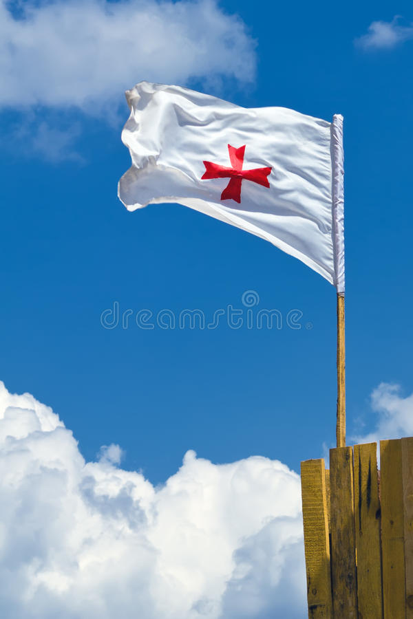 Templar flag. Medieval Combat Society. White flag with red cross waving in the wind against blue sky with clouds royalty free stock photography